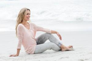 loira bonita sorridente relaxante na areia foto