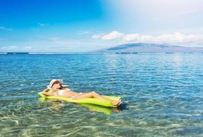 mulher relaxante e flutuando no oceano foto
