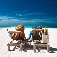 casal relaxa na praia de Maldivas