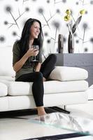 mulher relaxando em seu sofá com uma bebida foto