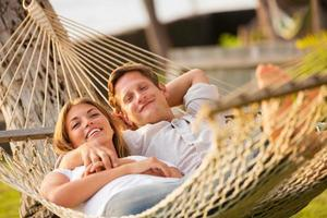 casal relaxando na rede tropical foto