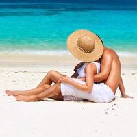 casal de branco relaxa em uma praia nas Maldivas