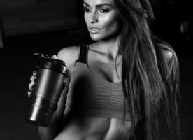 garota fitness com toalha e agitador relaxante no ginásio