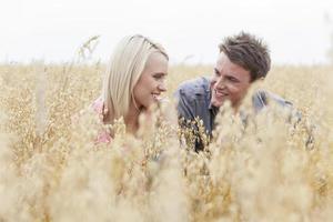 homem feliz olhando a mulher enquanto relaxa no meio do campo foto