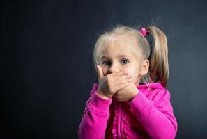 menina cobre a boca com as mãos foto