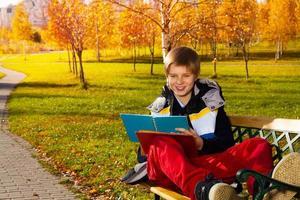 menino sorridente com livro foto