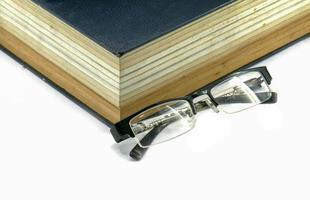livro de texto antigo ou Bíblia com óculos foto