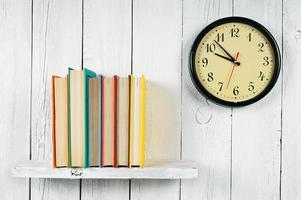 relógios e livros em uma prateleira de madeira. foto