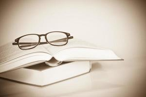 óculos de aros pretos colocados no livro aberto