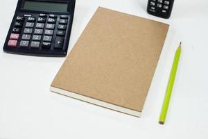 caderno com lápis sobre fundo branco foto