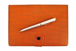 caderno com uma caneta de prata foto