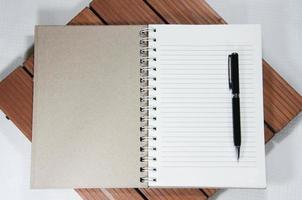 caderno branco em branco e caneta na madeira foto