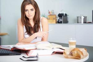 mulher jovem estudante com muitos livros estudando foto