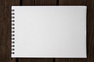caderno de bloco de notas espiral realista de papel em branco lagoa no banco de madeira foto