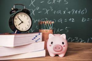 banco de porco e um relógio em um fundo verde foto