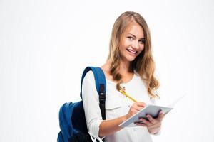 menina com mochila, escrevendo notas foto