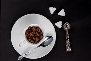 xícara de grãos de café torrados frescos na lousa preta foto