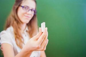 professor ou aluno, segurando um giz perto de lousa verde foto