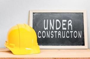 segurança do capacete com lousa (em construção) na mesa foto