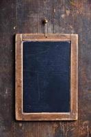 close-up de um quadro de giz ardósia pendurado em uma parede de madeira foto