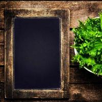quadro preto para menu e salada fresca sobre fundo de madeira foto