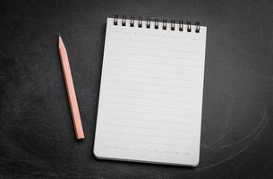 abra o bloco de notas em branco sobre fundo preto lousa com lápis foto