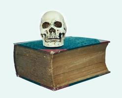 crânio e grande livro de texto antigo foto