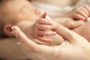 mão do recém-nascido, segurando o polegar da mãe