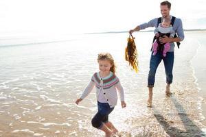 pai com filhos na praia foto
