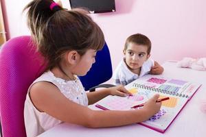 duas crianças estudando em casa foto