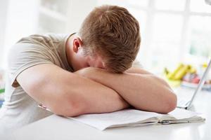 menino deprimido, estudando em casa foto