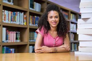 bonita estudante estudando na biblioteca foto
