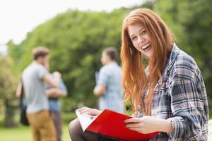 bonita estudante estudando fora do campus foto