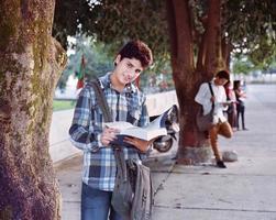 estudante do sexo masculino estudando perto do carrinho de estacionamento. foto
