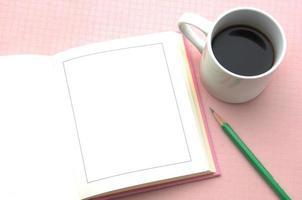 livro aberto e xícara de café sobre fundo rosa foto