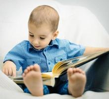 menino bonito, olhando o livro foto