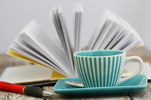 xícara de café com livro aberto no fundo foto