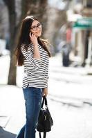 bela modelo caminha com telefone foto