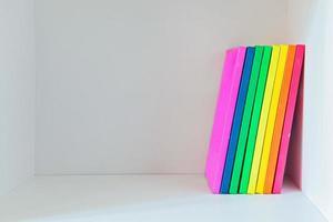livros multi-coloridos na estante de cor clara foto
