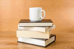 livros e xícara de café em uma mesa foto