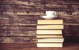 livros e xícara de café sobre fundo de madeira. foto