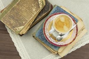 xícara de café em porcelana e livros antigos
