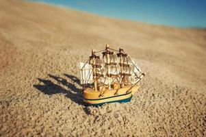 modelo de navio à vela na areia foto