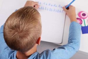 garoto escrevendo o alfabeto. crianças, lição de casa, conceito de educação. foto