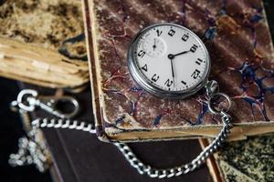 livros antigos e relógio de bolso