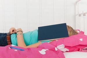 dormindo debaixo de um livro escolar foto