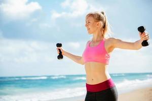 mulher de fitness com halteres malhando foto