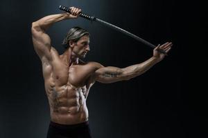 modelo masculino musculoso em estúdio com uma espada foto