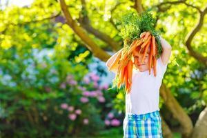garoto garoto engraçado com cenouras no jardim doméstico foto