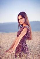 menina bonita no campo de trigo ao pôr do sol